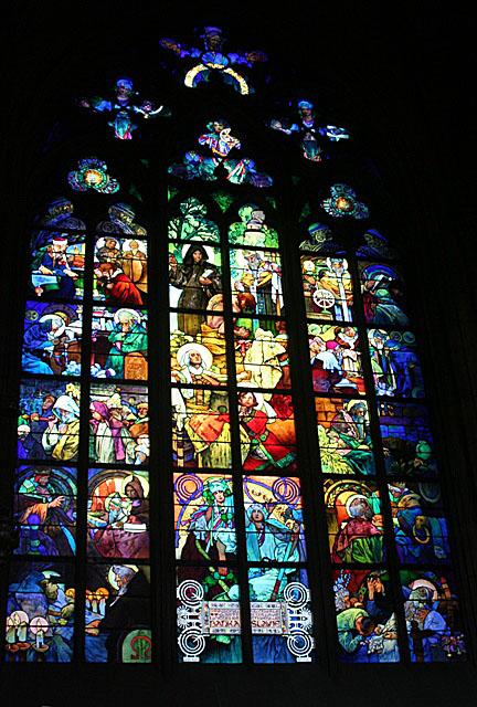 聖ヴィート教会のミュシャのステンドグラス <br /><br />日本でのミュシャ人気は年々高まっている。ミュシャ独特の感性で描かれた、その美しい装飾美と艶やかな女性たちは多くの人を魅了して止まない。そして、その大多数が好む作品はパリ時代に制作された装飾パネルやポスターの絵柄である。もちろん、これらの作品は耽美であり優雅であり、その当時から人気を博しているものばかりだ。しかし、ミュシャ芸術の真髄がどこにあるのか問うた時、それは別のところにあるはずだ。華やかな様相に包まれた作品とは一線を画したところに、ミュシャの静かな、そして激しい芸術家魂が潜んでいるのだ。そこにはスラヴ民族としての誇りを生涯持ち続けた、ミュシャの強い愛国心が深く交錯している。聖ヴィート教会のステンドグラスで最も人気の高いのが聖堂に入って左側三番目のステンドグラスの作品で、エルサレムの司教だった聖キリルの生涯を描いている。1931年製作。