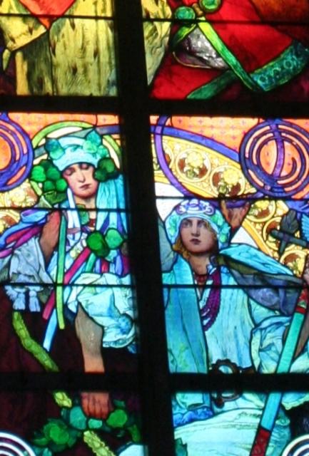 聖ヴィート教会のミュシャのステンドグラス <br /><br />上写真の下の部分中央付近をアップでとらえた物です。このステンドグラスには、タイトルがついていて、「聖キリルと聖メトリウスの生活」なんだそうです。この聖キリルと聖メトリウスは、このボヘミアに初めてキリスト教を伝えた宣教師である、ギリシャ人兄弟の名前なんだそうです。日本で言えば、あのフランシスコ・ザビエルみたいな人ですね。この聖キリルと聖メトリウス兄弟がどこにいるかと言うと、このステンドグラスの一番下の真ん中にいる青い衣をまとった二人組みが、そうなんだそうですよ。ミュシャのステンドグラスは聖ヴィート教会ではこれが一番すきです。色使いもいいし女性が素晴らしくいきいきと描かれていますね。写真をゆっくりと撮っているゆとりはなかったのですがズームでアップして撮りました。 <br />