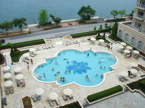 バルコニーから下を見ると既に屋外プールがオープンしており、夏らしい湖畔のリゾート風景になっている。