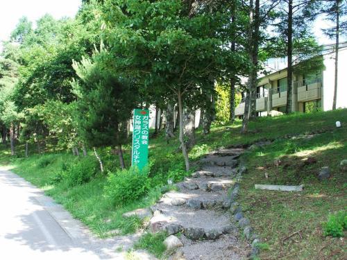 この道を通って女神湖の周回道路に降りる。カラマツの林の間から見える建物はアネックス?号棟。