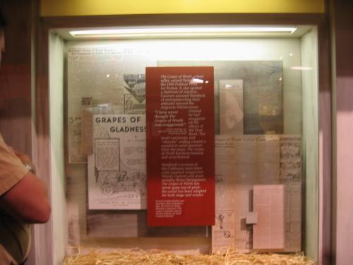 """「怒りの葡萄」(1939年)関連の展示。<br />「Grapes of Gladness」は、この作品を単なる社会小説とみて、心よく思わない農園主や地元の人のために書かれたパンフレット。オクラホマの貧農、Okiesを労働力に受入れたカリフォルニア、彼らを送り出したオクラホマや他の中西部の州でもアメリカの価値観を損なうものとみられた。'90年代でも、地方自治が強いので、学校の図書館から取り除かれ、禁書扱いにする教育委員会がある。<br />しかし、一方、スタインベックの宗教心をPreacherのJohn Casyやジョード一家に読み取る教師や、旧約聖書のモーゼの出エジプト記に重ね合わせて読み取る研究者もいる。 ジョード一家は、連邦政府の作ったシェルターからあえて出て行き、娘のRose of Sharonは赤ん坊を亡くし、究極の人間愛の結末を迎える。スタインベックは、最終ページの構想を、絵画、Cimon & Pero:Roman Charity*から得たのではないかともいわれている。<br />1940年にルーズベルト大統領夫人が現地を視察し、事実は、本以上だとスタインベックに手紙を送っている。<br /><br />次の関連サイト、「名残りのルート66」をご覧下さい。<br />http://4travel.jp/traveler/bluebonnet/album/10057541/ <br /><br />*この絵画は、ヨーロッパで数多く描かれています。Rubensのものが、アムステルダム国立美術館で見られます。<br />ちなみに、ジョンフォードの映画では、川に流される赤ん坊の亡骸と最終ページの納屋のシーンはありません。連邦政府のキャンプを出ていく車の運転席の正に""""Great Mother""""がエンディングになっています。<br />"""