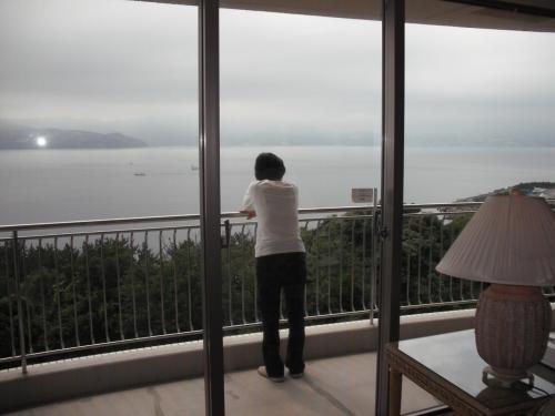 バルコニーからの眺め(写真)。残念ながら天気が悪く、青い海は見えない。リビングルームの天井にスピーカーがあり、2種類のBGMが聞ける。イージーリスニングの音楽を聴きながらコーヒーを飲む。幸せの一瞬。<br />
