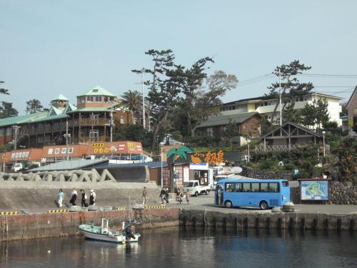 初島港到着。平日なのに結構賑わっている。釣り人、観光客‥‥。ブルーの車体のエクシブのシャトルバス(写真)に乗り込む。