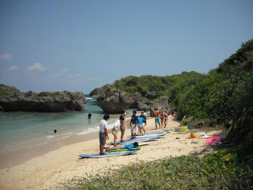 しかも、ほとんどが20才前後の若者に見える。9月上旬、まだ大学は夏休みで学生さん達は夏休みを沖縄の海でエンジョイしているようである。我々の目の前でサーフィンスクールの一団(写真)が練習をはじめる。