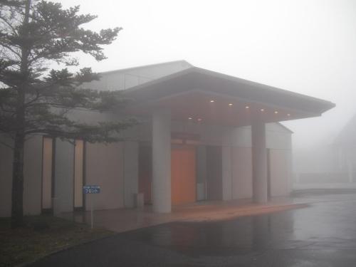 霧に包まれたホテル玄関(写真)に車を寄せて自分で荷物を運ぶ。最悪の高原リゾートを最高に楽しもう!(自分を鼓舞する)