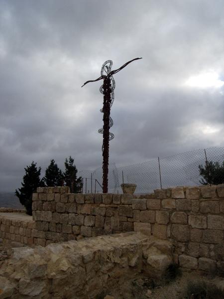 山頂には、十字架にかけられたイエス・キリストを表すとも、モーセの「ブロンズの蛇」を表すとも言われるモニュメントがあります。「ブロンズの蛇」とは、モーゼが神の命により作って掲げていたもので、人々はそれを見ると、毒蛇にかまれても死ななかった、というエピソードが聖書にあります。いまやネボ山のシンボルのようになっていますが、近代にイタリアの彫刻家が作ったものです。