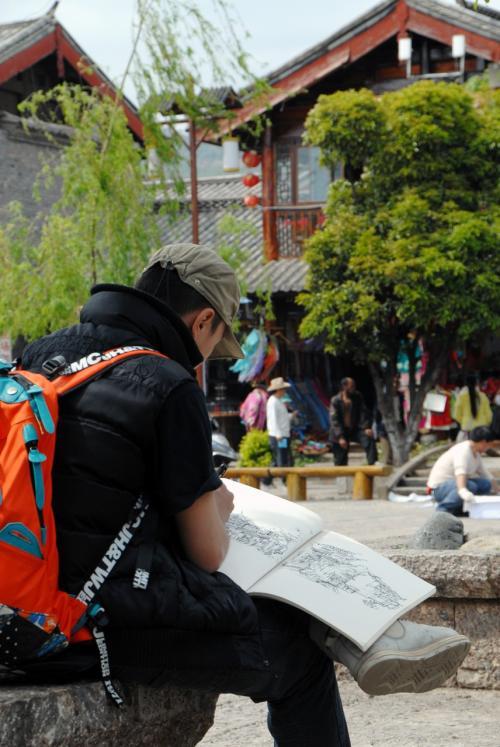四方街の真ん中に座って写生する青年。<br /><br />なかなかの腕前ですね!