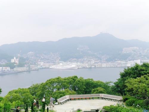 長崎湾と稲佐山(霞んでいますが電波塔がある一番高い山)<br />湾内が狭いため、昔、巨大タンカーの進水式で、船台から滑り降りた船が対岸にぶつからないための苦心の物語を映画で見たことがあります。<br /><br />岩波映画「巨船ネス・サブリン」1961年制作 42分<br />昭和30年代、日本の造船界は原油輸送のための大型タンカーブームが始まった。造船と経済成長の始まりを象徴する建造記録の代表作。三菱造船・長崎造船所で建造された巨大タンカー「ネス・サブリン号」は、8万7000トン、長さ254m、幅37mという、まこと巨船の名にふさわしいもの。この巨大船の設計から進水、処女航海にいたるまでのプロセスを、技術陣や現場作業員の労苦と愛情を織りまぜながら克明に描いてゆく。<br />注:この映画のDVDは現在購入可能です。<br />http://www.amazon.co.jp/%E9%87%8D%E5%8E%9A%E9%95%B7%E5%A4%A7%E3%83%BB%E6%98%AD%E5%92%8C%E3%81%AE%E3%83%93%E3%83%83%E3%82%B0%E3%83%97%E3%83%AD%E3%82%B8%E3%82%A7%E3%82%AF%E3%83%88%E3%82%B7%E3%83%AA%E3%83%BC%E3%82%BA-%E5%B7%A8%E8%88%B9-%E3%83%8D%E3%82%B9%E3%83%BB%E3%82%B5%E3%83%96%E3%83%AA%E3%83%B3-DVD-%E3%83%89%E3%82%AD%E3%83%A5%E3%83%A1%E3%83%B3%E3%82%BF%E3%83%AA%E3%83%BC/dp/B000THOY6K