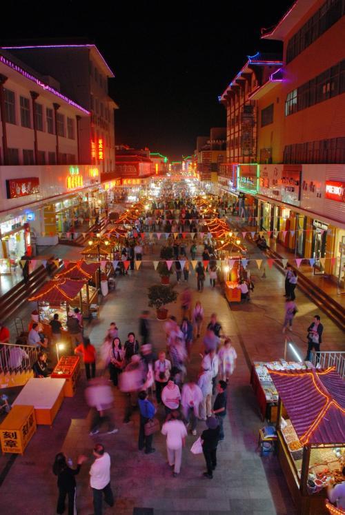 09/13:敦煌市内〜夕方鳴沙山。<br /><br /><br />商業一条街風景「夜景」。<br /><br />再度こま定番のポイントから。<br /><br /><br />手前に見えている人の塊は「日本人観光団体客」。<br />ガイドに色々伝えられていましたが、15分程かかっていました。<br />その後、奥の夜市へ向かうでもなく、左手の小吃広場へ行くでもなく、みんな手前の方へと歩いて行きました・・・<br />折角の自由時間なのに、ホテルへ帰っちゃったんです!!<br />ガイドが「スリや強盗に注意!」みたいな事でも言ったのでしょうか。安全第一と言う事から見れば仕方がないのかも知れませんが、別に敦煌でなくても、スられる時はスられるし、事故に遭う時は遭います。<br />敦煌の夜市を歩かないなんて、こま的には信じられません!