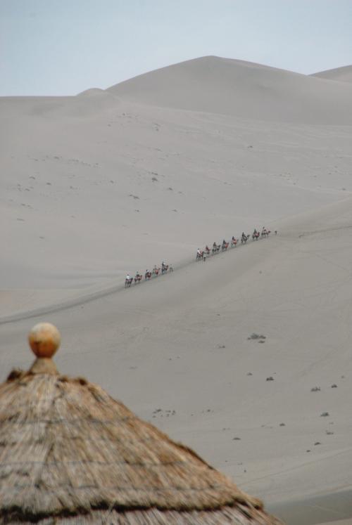 鳴沙山の頂上へ向かう駱駝隊。<br />