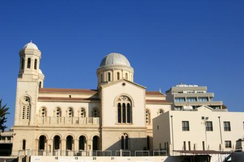 2日目、方向音痴スペシャリストな私もさすがにもう道に迷わず目的地へ歩いていけますよ〜〜<br />写真はAgia Napa(聖ナパ教会)なかなか外観は立派で美しい教会で興味はあったが、そんな時間の余裕もないのでスタスタと素通り<br />目指すiインフォーメーションはこの教会を左目に見ながら通り過ぎてすぐの場所にあり、今回は迷う事なくスムーズに到着(迷いようがない位分かりやすい場所にありますからね)<br />iのドアを開き奥にいた女性に挨拶し早速レンタサイクル屋の場所を訊ねてみる。するとこれまたちょっと首をかしげながら地図を広げ「近所にはないからここからバスに乗ってしばらく行った場所にならレンタルサイクルショップがあるわよ」との回答<br />出発前レンタルサイクルを利用した人の情報をネットでよく目にしていたので、てっきりレンタルサイクルショップなんてそこら辺に何軒かあるんだろうと簡単に思い込んでいた私はここでもまた出鼻をくじかれてしまうorz・・やっぱ最初からレンタルサイクル設備のあるホテルに泊まっとけばよかったと後悔するがこれまた後の祭り。<br />「私は猫修道院に行きたいんですがやっぱタクシーで行ったほうがいいですか?」と聞いてみると(聞くまでもなく答えはわかっているが)「そのほうがいいでしょうね、バスで途中までは行けてもそこからは歩いていくしかないしあの辺りはなにせ英領アクロティリ・デケリアだからね・・」との事<br />今からバスに乗ってまでレンタサイクルをしに行く時間のほうがよほどもったいないし何より面倒くさいので此処でもいさぎよくタクシーチャーターを決意<br />iの女性は手際良く近所のタクシー会社に手配をしてくれチャーターにかかる料金の確認やタクシー会社の名前と行き先を書いたメモを渡してくれた。<br />ちなみに料金は1時間ほどのチャーターと想定して往復60ユーロ也<br />ちょっと痛い出費ではあるが、私にとってキプロスまで来て猫修道院に行かないなどという選択肢などあり得ないのだから背に腹はかえられない<br />