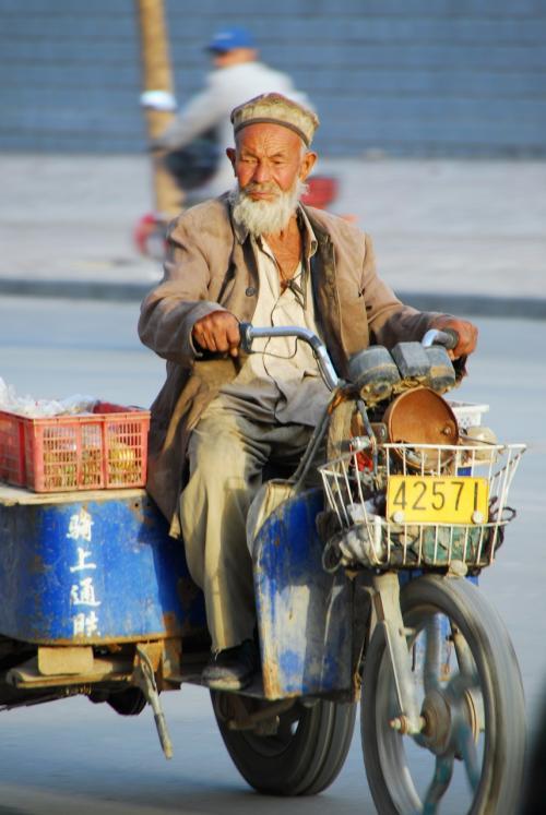 莎車(ヤルカンド)の古勒巴格路を疾走(?)していた三輪バイクのおじさん。<br />ピノキオに出てくるゼペット爺さんみたいな・・・^^