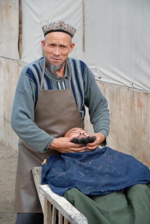 莎車の回城老街で見た露店散髪屋。<br /><br />お客の鬚を鷲掴みして、まるでモップでも作っているかの如く〜♪(前に引っ張り出す髪型(鬚型?)が定番のようです!)
