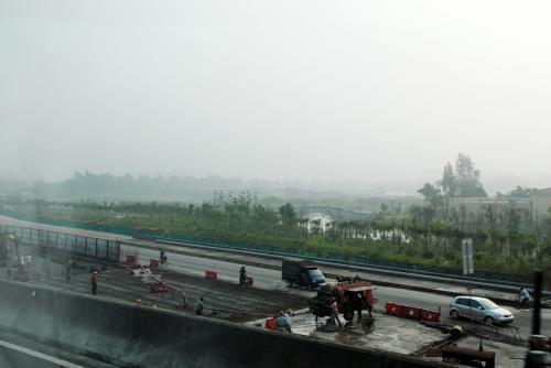 空港までの間、天気も悪いので写真無し。<br /><br />もうすぐ空港ですね。<br />この辺りの環境美化も急ピッチ!!