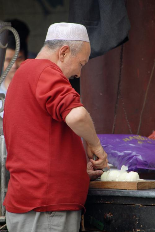 タマネギをきざむ司馬義おやじ。<br /><br />抓飯の下味ですね。<br />後で戴きますので、じっくり煮込んで下さいね。