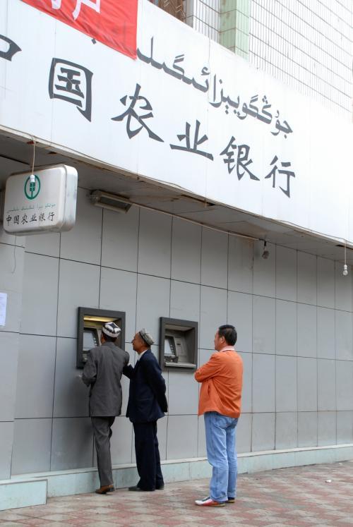 出て直ぐの所にある農業銀行のATM。<br /><br />表示は維吾爾語もOK!<br /><br />以前北京でみた可哀想な光景を思い出しました。<br />ATMではありませんが、一人の維吾爾人男性が、中国銀行から故郷へ送金しようとしていました。送金時、自分の名前を「直筆」する必要があったのですが、その人は漢字が書けません。彼は北京に出稼ぎに来ているか何かだったのでしょうけど、維吾爾文字だと、都会での手続きが出来ないので、田舎では誰かに書いて貰ったのでしょう。<br />男性は行員に「代筆」を頼みましたが、行員は「本人でなければ駄目」と言い張り書いてくれません。何度も頼んでいましたが、解決方法は無いという感じ。<br />結局諦めて行きましたが、多民族国家のくせして、少数民族用特別処置の対応もないのか・・・と、情けなく感じました。<br />口先だけの民意重視「執政為民」、実際はナンにも考えてないという証明ですね。<br /><br />しかし新疆地区では、きちんと維吾爾文字が対応されているので、これも矛盾ですよね。
