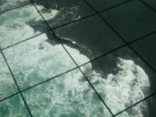 畳1枚くらいの大きさのガラス床から海面を見ると、水の流れに段差(写真)ができている。これは海底の岩で出来た段差ではなく急激に満潮から干潮に変わる時に生じる自然の水の落差という。