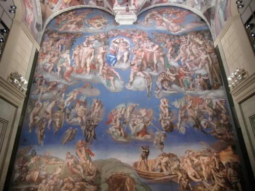 システィーナ礼拝堂の天井画完成からおよそ四半世紀後、ミケランジェロは同じ礼拝堂の奥壁に『最後の審判』(写真)を描いた。(1536-41年制作)<br />本物の礼拝堂は超満員であるがここではゆっくり鑑賞できる。