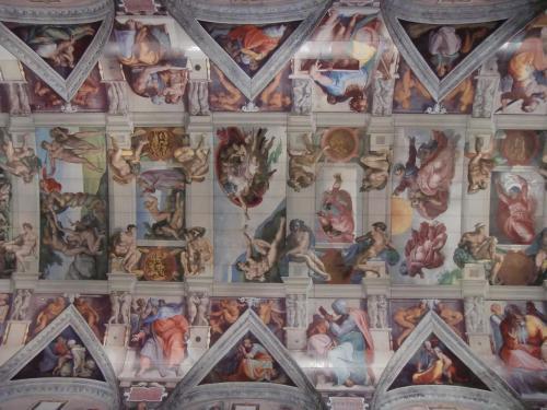 システィーナ礼拝堂の天井画(写真)は教皇ユリウス2世の命によりミケランジェロがほとんど助手も使わずに1人で完成させたという。絵の内容は「天地創造」「人類の誕生」「人類の堕落と刑罰」等。(1508-12年制作)ベンチに寝転がって天井画を鑑賞する。