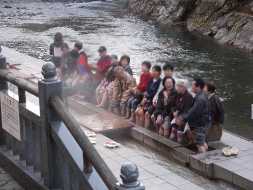 河原で気持ち良さそうに足湯を楽しむ観光客。源泉温度の高い温泉に行くと、こうして惜しげもなく河原などに足湯が設置されている。逆に冷やさなければ温泉を利用できないからだ。