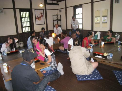 両子河原座の中で食事する留学生たち。