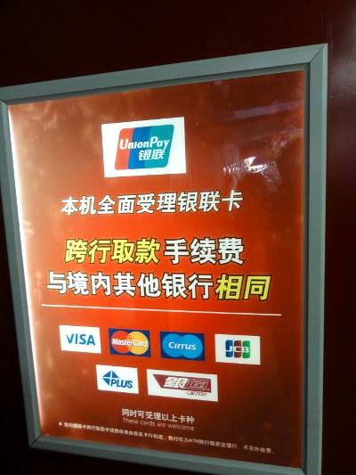 参考に中国銀行と工商銀行の情報を載せておきます。<br /><br />中国銀行:<br />同城同行ATM同じ町の同じ銀行): 無料<br />同城跨行ATM(同じ町の違う銀行): 4元(50円)<br />異地同行ATM(違う町の同じ銀行): 10元(120円)<br />省外跨行ATM(違う省の違う銀行): 12元(145円)<br />参考: http://www.boc.cn/bcservice/bc3/bc31/201107/t20110718_1456893.html<br /><br />工商銀行:<br />同城同行ATM同じ町の同じ銀行): 無料<br />同城跨行ATM(同じ町の違う銀行): 4元(50円)<br />異地同行ATM(違う町の同じ銀行): 金額の1% (最低2元 - 最高100元)<br />異地跨行ATM(違う町の違う銀行): 4元(50円) + 金額の1% (最低2元 - 最高100元)<br />参考: http://www.sz.icbc.com.cn/zytg/2011-04-20/45717.html<br /><br />大雑把にまとめると、<br />同じ町の同じ銀行: 無料<br />同じ町の違う銀行: 大手が4元(50円)、その他は2-4元(25-50円)。中小では、最初の2回まで無料とかもあります。<br />違う町の違う銀行: 固定費(2-4元 = 25-50円) + 比例分(金額の0.5-1.0%)というのが主流。<br />** 大手の中では、中国銀行のみ比例分がなく固定費12元(145円)だけす。一度に1000元(12000円)以上下ろすと、一応割に合う計算です。<br /><br />違う町の同じ銀行: こちらも比例分(金額の0.5-1.0%)というのが一般的。<br />** つまりホームタウンを離れると、自行と他行の引き出し手数料の差は、少額の固定費(2-4元)でしかないのです。ここでも中国銀行は10元で固定。手数料無料またはそれに近い銀行もありますが、たいてい支店の少ない銀行です。<br /><br /> こう見てみると、いかに人民が銀行から搾取されているかわかります。ところでこの料金体系、どこかで見覚えありませんか。そう、携帯電話のプランです。市内なら、相手が他のキャリアでも激安なのに、一歩、市外に出ると別の料金体系、さらに省外に出ると別の料金プラン。広大な中国では、あらゆる分野に地域主義が根ざしているようです。