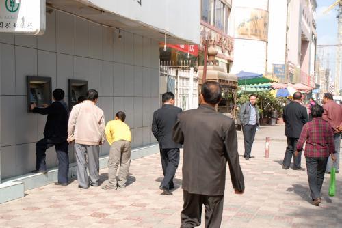 少し北上して、招待所へと向かいます。<br /><br />今日は何かの支給日で、ATMに人が並んでいました。<br />都会ではもう見かけない「壁に直接設置」されたATM。