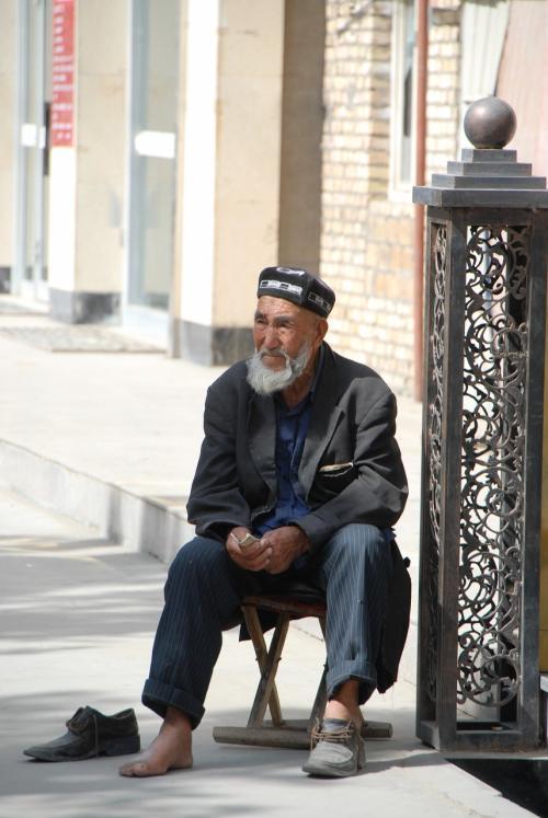 宿の前でのんびりしている維吾爾爺さん。<br /><br />何故か片方の靴を脱いでいます。