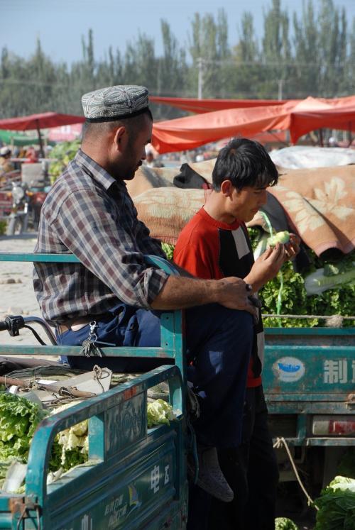 林檎を囓ってる若手の維吾爾人。<br /><br />彼らも野菜を売っていました。<br /><br />