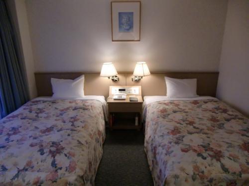 本日の部屋はアネックス?号棟4階のツインルーム(写真)。窓を開けると小さなバルコニーがあり、女神湖、蓼科山が見える。