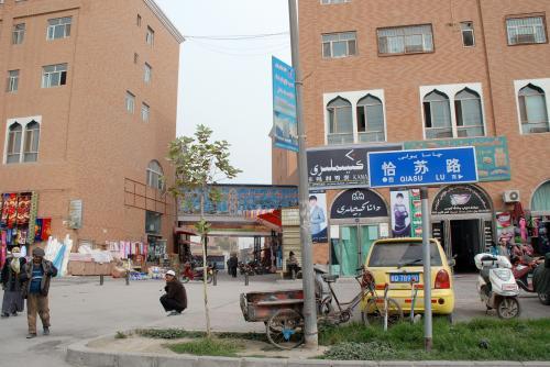 あっと言う間に「恰蘇路」です。<br /><br />針金鬚オヤジの帽子店は、この蘇碧恰大巴扎のビルが切れている所の奥にあります。