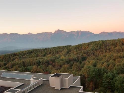 朝日が南アルプスの高峰「北岳(3193m)」「仙丈ヶ岳(3033m)」(写真)を赤く染める。手前は八ヶ岳山麓の広大な尾根でカラマツが密集している。