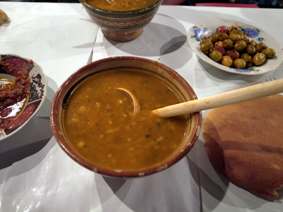 モロッコ名物の一つ、豆が入ったハリーラと呼ばれるスープです。ヒヨコ豆、レンズ豆をつぶしたものが入っていて、ものによってはややスパイシー。こんなふうに、大きなしゃもじのようなスプーンで食べます。これと丸いパンだけで、結構なボリュームになります。