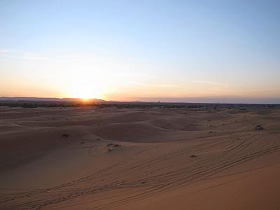 砂漠の夕日。ここの砂漠の砂は本当にサラサラで、絵に描いたような「砂漠!」という光景を見ることができます。夕日が地平線に近づくにつれて、クリーム色だった砂が次第に赤く染まっていきます。まさに感動的です。