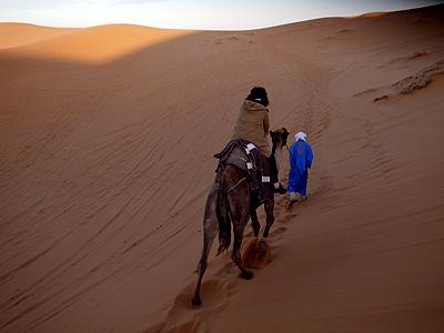 そして朝のラクダツアー。これはもう日が出てからですが、こんな風にラクダに乗り、砂丘の頂上を目指します。砂丘の上のほうはとっても砂が細かく、普通に歩いていると足がずぶずぶと沈んでしまいます。すたすた歩けるのは、ラクダやベルベルのおにーさんだから? <br />ラクダは頂上までは行けないので、情けないことに、最後の10メートルほどは、おにーさんに手を引っ張ってもらって進むことになります。<br />ちなみに後で気づきましたが、裸足になるとだいぶ歩きやすいです…。