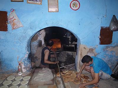 パン屋さんの窯。昔ながらの石の窯で、平たいところにガンガン突っ込んでいきます(日本で見る、ピザ屋の石窯を大きくしたようなものですが)。<br />まんなかのおじさんは、燃え盛る窯の前にずーっと立っていて、次から次へとパンを出し入れしています。そのワイルドな仕事ぶりに、思わずほれぼれしてしまいます。<br />