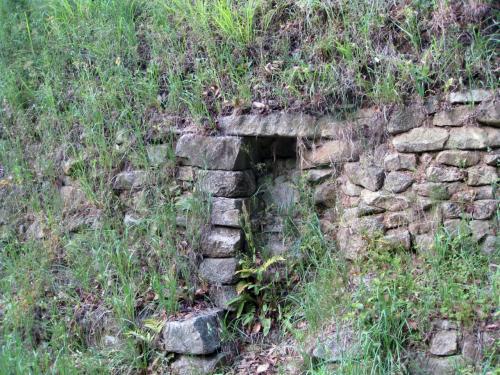 さらに奥へ、日本最古の朝鮮式山城、[大野城跡]へ。 白村江の戦いで大敗したあと、大宰府を守るために朝鮮式山城を、この地に築く。 急峻な土塁跡が林道脇に見える。 四王寺山の尾根に築かれた土塁は全長約8kmで、二重の土塁が設けられている。 城の内部には70棟に及ぶ倉庫があったようで、そのうちの礎石跡などに案内される。 662年、白村江の戦いに大敗したあと、わずか1年で水城を含む大野城が造られたそうだ。