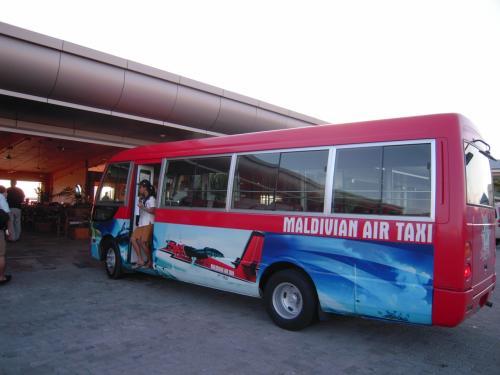 国際線ターミナルのチェックインカウンターから、水上飛行機乗り場のターミナルまでは赤いバスで移動。<br />空港を半周します。移動中右手にはマーレの首都が見えます。