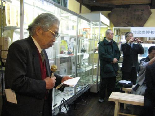 地名研究会 吉田金彦会長 開会式の挨拶 <br /><br /> 本館は民家の良さを生かし天井の小屋組を見せて古材の木や竹を駆使し、別館は本格的土蔵作りの内部を利用した展示室です。幾世代にもわたり風雪に耐えてきた日本の民家は、経済・社会構造や生活様式の変化のなかで取り壊され失われようとしています。伝統的な日本の民家は、地元に育った木と地域の人々の技術で造られた住いであり「日本の住文化」の結晶といえます。<br />
