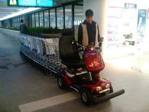 シニアカーのような電動カーでカートを運んでいました。