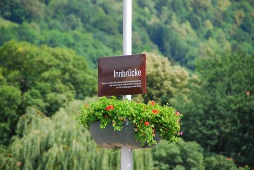 イン川に架かる橋、その名も「イン橋」。そのまんまだ。<br /><br />花のバスケットで飾られた橋の看板。
