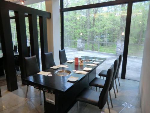 店内はそれ程広くはない。ホテル裏庭の森に面して焼肉テーブル席(写真)が並んでいる。