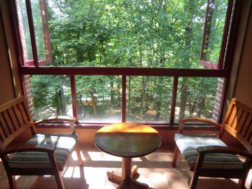"""テラス席の窓(写真)は全開でき、森の新鮮な空気を胸いっぱいに吸い込める。夏の午後、ここに座って""""木漏れ日の下で読書""""なんていうのはどうだろうか?"""