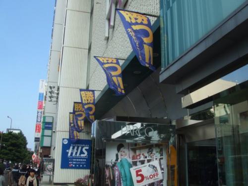 お腹も一杯になったところで、いざスタジアムへ。連絡バスに乗るためにパルコ前に行くとまたしてもこの旗が・・・。
