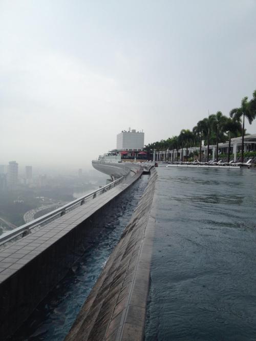プールに入りに来たら、突然の嵐。ものすごい雨と風。みんな慌てて撤収。せっかくなのでビーチタオルを確保してしばらく待っていたら、雨風が弱くなってきた。では、ということで誰もいないプールに入る。この天空のプールをほぼ独占状態という贅沢。<br />これは、プールの端から撮った写真。プールサイドから見るとプールの先は何も無いように見えますが、実際には一段下がったところにあふれた水が流れるところとフェンスがあります。いわゆるインフィニティープールは、だいたいこのような構造ですね。