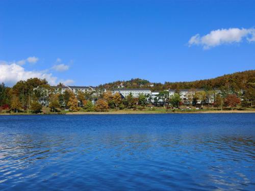 女神湖に到着し、まずは湖畔を歩いて1周する。今日の女神湖はいつになく青く、「ホテルアンビエント蓼科」(写真)も輝いている。<br />