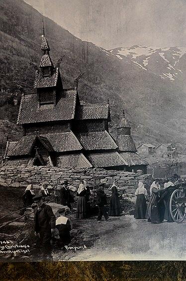 ボルグンのスターブ教会の古い写真も展示されてあったビジター・センター。<br /><br />左下に 1907 と書かれてあるのは、1907年撮影の意味かな。<br /><br />教会の外観も特徴的ですが、この画像では村の人々のいでたちも目に止まります。<br />女性は全員、大きいスカーフ+長いドレス姿だったのね。<br /><br />あれ? 画像手前から向こうに歩いて行く男の子が着ているのはセーラー服? 水兵さん風の帽子までかぶっちゃって。