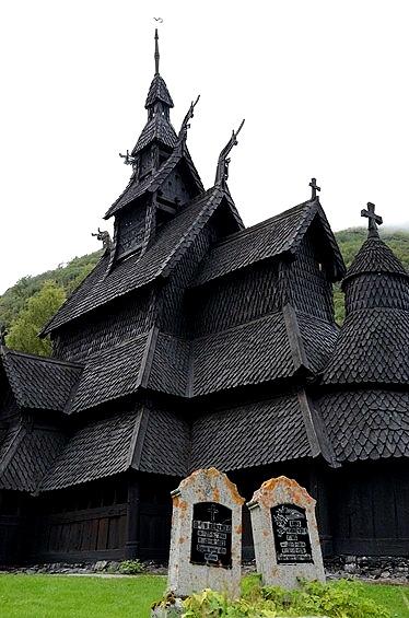 近づいて行ってみると、石垣に囲まれたボルグンのスターブ教会は道路よりも一段高い場所にあるため、こんな角度で見上げることが出来ました。<br /><br />教会の敷地は墓地になっていて、墓碑も並んでいます。<br /><br /><br />この画像では分かりにくいんですが、教会の塔の先には風見鶏が乗っていて、更に先端には小さい十字架がありました。<br />