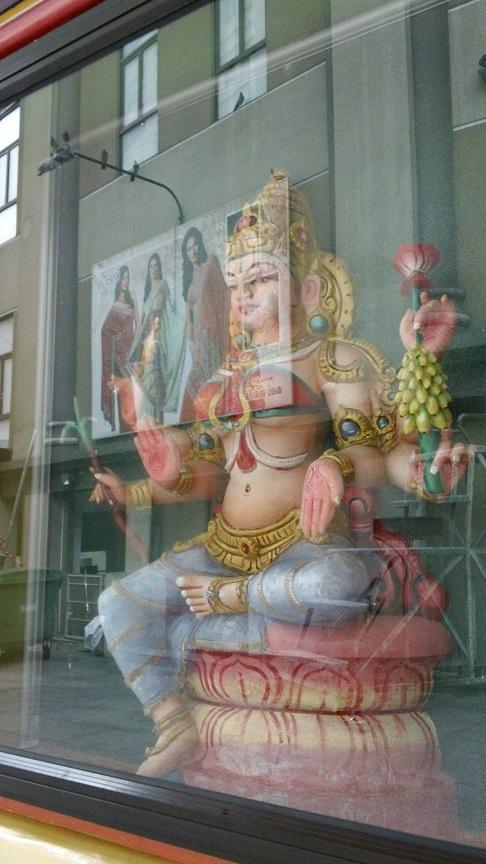 宗教的な像の飾られたガラスに向かいの<br />インド系ショッピングモールの洋服屋の<br />広告が映る。<br /><br />こんなところも、俗と聖が堂々と混在している<br />ヒンドゥー文化を象徴している気がした。