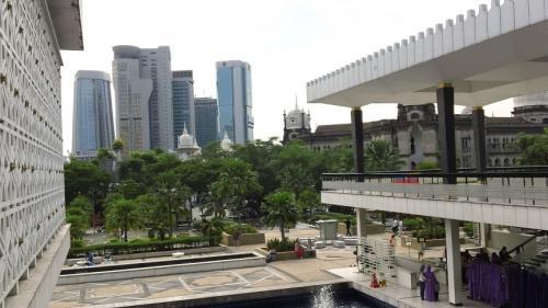 上の階からはちょうどバックにKLの高層ビルが<br />見える。バンコクの高層ビルと仏教寺院もそうだが<br />「こうやって近代的なモノと伝統的なモノが同居して<br />いるのがカッコイイ!」と思って写真に撮ろうと<br />したら、なんと下の階にメインの入り口があることに<br />気が付いた!!<br /><br />よくは見えないが受付のようなモノがあり、貸衣装や<br />記帳ブックもある。人も多い。俺が入って来たところは<br />守衛のような人が2人しかいなかったのに。俺はどうやら<br />正式な玄関でなく横玄関から入ってしまったらしい。。orz <br />でも守衛がこっから入れと言ったのだしな〜。。信者だから<br />いいかと思われたのかw <br /><br />ま、いいや。目的の用事は終わったし。でも正面のほうも<br />行ってみたい。ミヤゲモノ屋があるのも見えたし。くつを<br />横玄関に置いてきていたので、急いで入って来たところに<br />戻り、守衛2人に礼を言ってくつを履いて正面玄関に回る。<br /><br />そこでもアラビア語で挨拶したが、やはり受付の人たちは<br />うなづきはするけどアラビア語では返して来ず。もう慣れた<br />ので深く考えず、「アメリカから来た観光客だけどムスリム<br />だ」と同じことを繰り替えす。また「もう見学は済ませて<br />来たけど、その奥の土産物屋が見たいのだ」と言う。「記帳を<br />していけ」というのでまたアラビア語でサインをしたら<br />「ムスリムか?」と訊いて来たので「そうだ」と答える。<br />「あがってください」というが、もう見学してきたので<br />断り、店だけ見に行く。